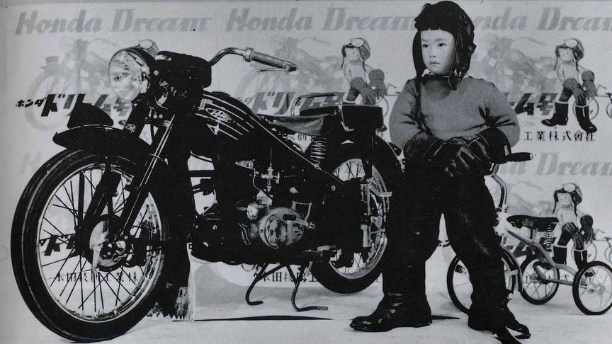 Honda vintage motorcycle three quarter front view and young rider standing.