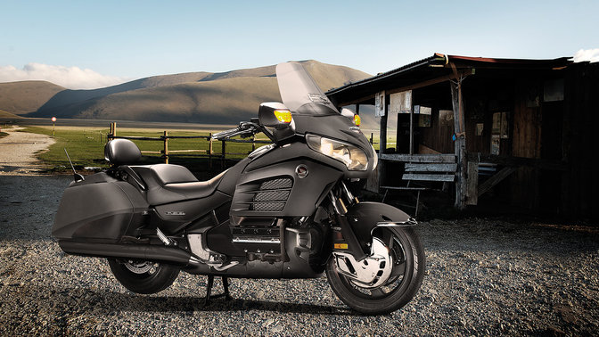 Front 3-quarter view of Gold Wing F6B parked with rider leaning on it. (rural location).